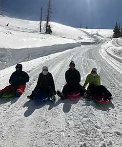 group sledding down snowy road